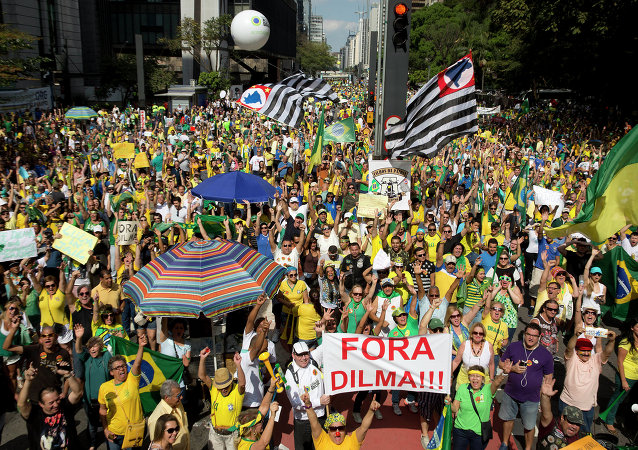 Demonstrators hold a sign that reads in Portuguese Dilma out during a protest demanding the impeachment of Brazil's President Dilma Rousseff in Sao Paulo, Brazil