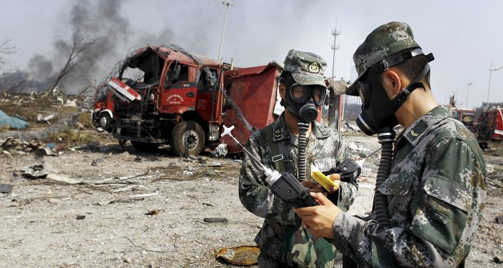 Soldiers of the People's Liberation Army anti-chemical warfare corps work next to a damaged firefighting vehicle at the site of Wednesday night's explosions at Binhai new district in Tianjin, China