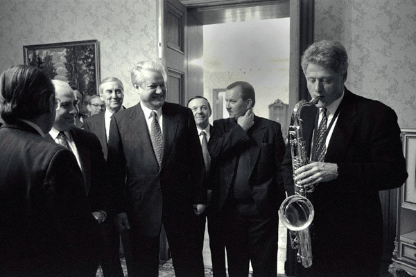 President Bill Clinton plays the saxophone presented to him by Russian President Boris Yeltsin at a private dinner hosted by President Yeltsin at Novoya Ogarova Dacha, Russia