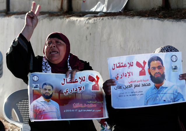 Supporters of Mohammed Allaan, a Palestinian prisoner who is on a long-term hunger strike, hold portraits of him during a sit-in calling for his release outside the International Committee of the Red Cross (ICRC) offices in Jerusalem, on August 11, 2015