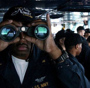 US Navy sailor CW02 Ernest Jackson, 42, of San Diego, California, peers through binoculars from the bridge of the USS Nimitz on Tuesday, June 5, 2007, in the Persian Gulf, where the Nimitz and the USS John C. Stennis aircraft carrier groups are on patrol