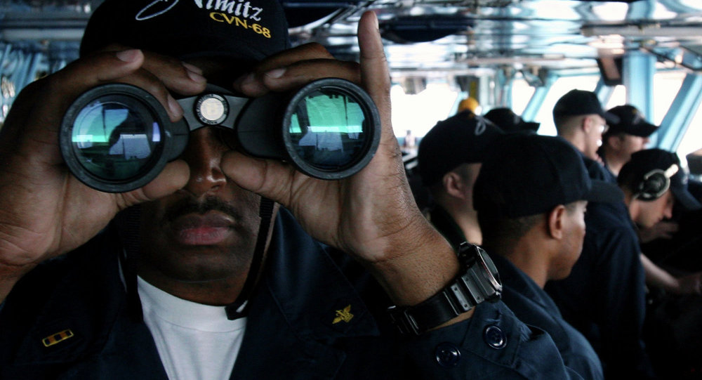 U.S. Navy sailor CW02 Ernest Jackson, 42, of San Diego, California, peers through binoculars from the bridge of the USS Nimitz on Tuesday, June 5, 2007, in the Persian Gulf, where the Nimitz and the USS John C. Stennis aircraft carrier groups are on patrol