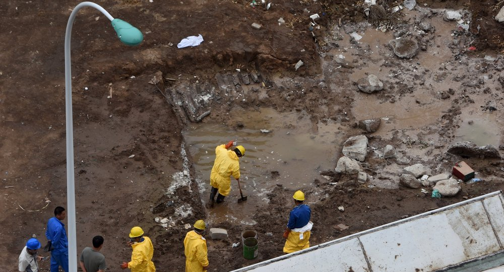 Rescue workers remove water polluted by chemicals from the site of explosions at the Binhai new district, Tianjin, China, August 19, 2015