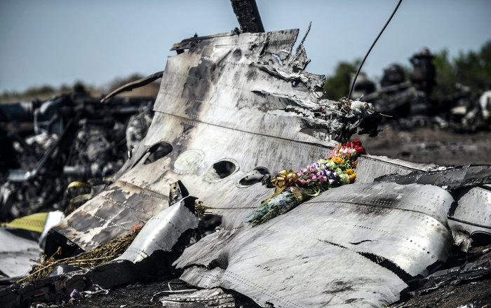 This photo taken on July 26, 2014 shows flowers, left by parents of an Australian victim of the crash, laid on a piece of the Malaysia Airlines plane MH17, near the village of Hrabove (Grabove), in the Donetsk region.