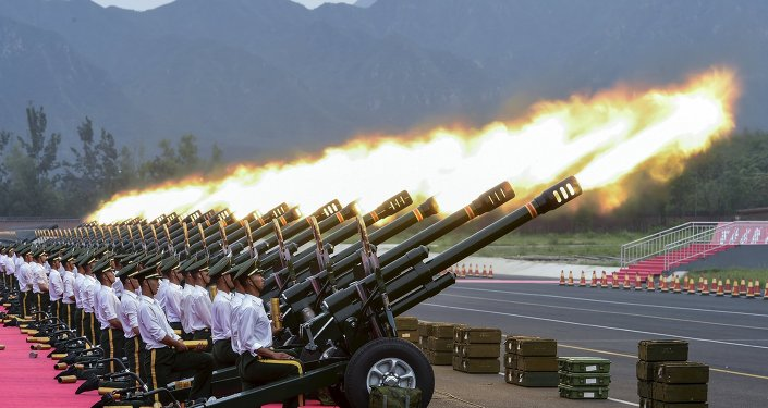 Paramilitary policemen and members of a gun salute team fire cannons during a training session for a military parade to mark the 70th anniversary of the end of the World War Two, at a military base in Beijing, China