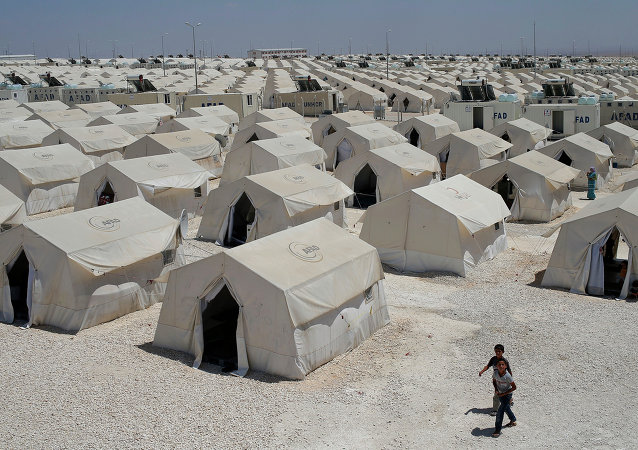 Syrian refugees wander around a refugee camp in Suruc, on the Turkey-Syria border, Friday, June 19, 2015
