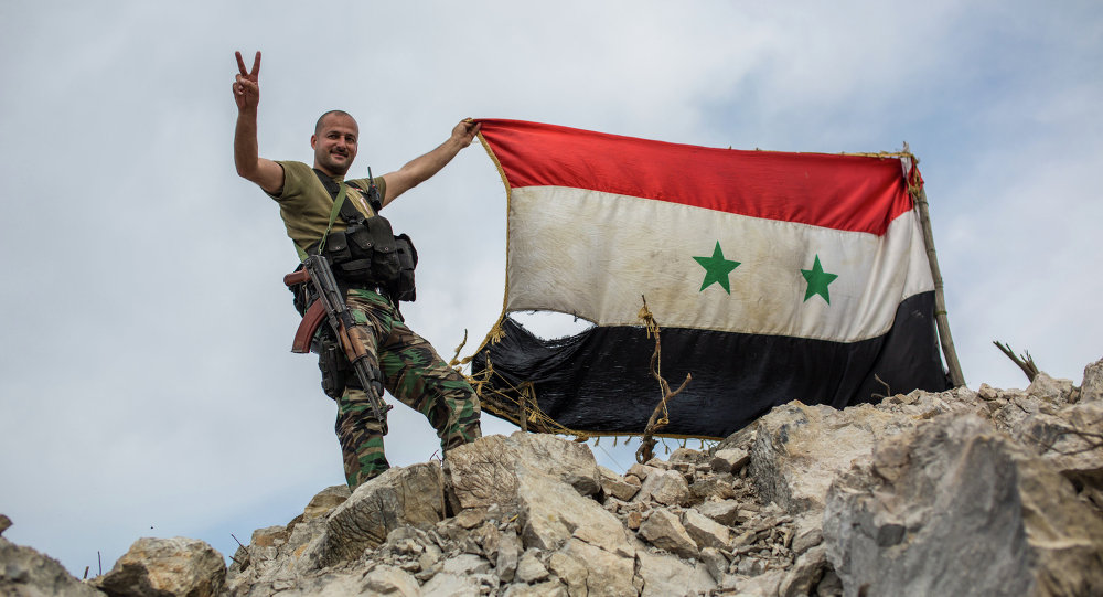 A government soldier with the Syrian flag on a location on top of a hill not far from Kessab on the Turkish border following an Islamist takeover of the town