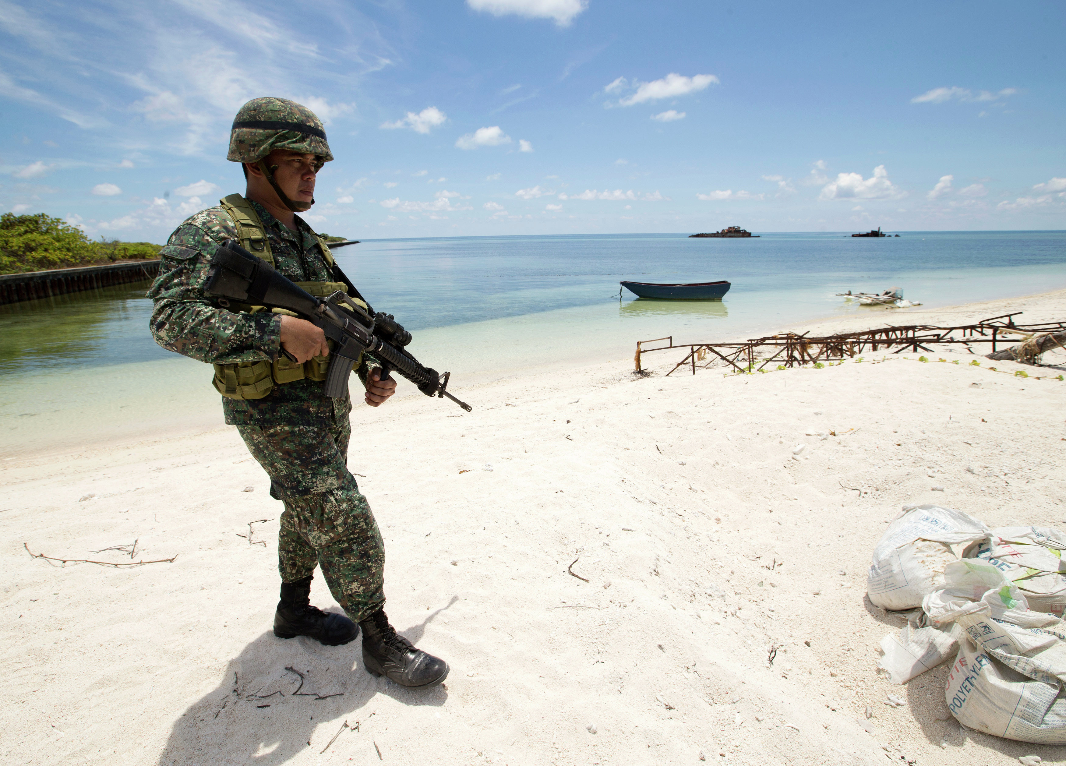 A Filipino soldier patrols the shore of disputed Pag-asa Island in the South China Sea.