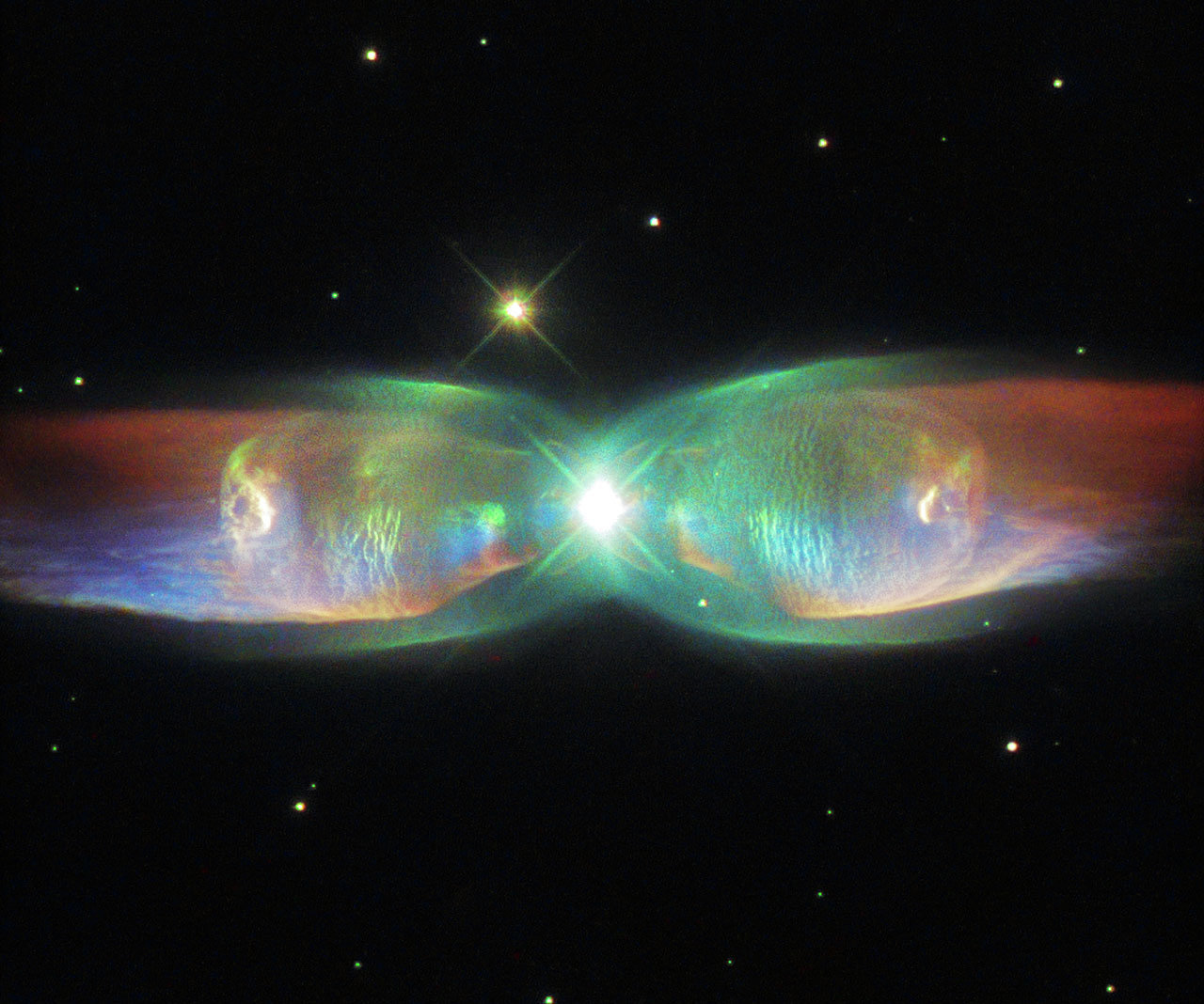 The shimmering colors visible in this NASA/ESA Hubble Space Telescope image show off the remarkable complexity of the Twin Jet Nebula.