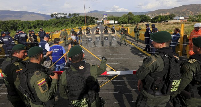 Colombian policemen stand guard in front of the border with Venezuelan policemen Bolivarianos near Villa del Rosario village, August 27, 2015
