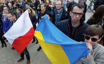 People holding a Poland flag, left, and a Ukraine flag listen to speakers during a demonstration in Warsaw, Poland showing their support for protesters in Ukraine