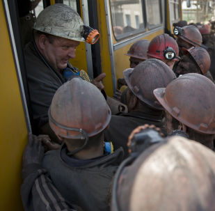 Ukrainian coal miners jokingly block a colleague from the next shift from getting off a bus at a coal mine outside Donetsk, Ukraine