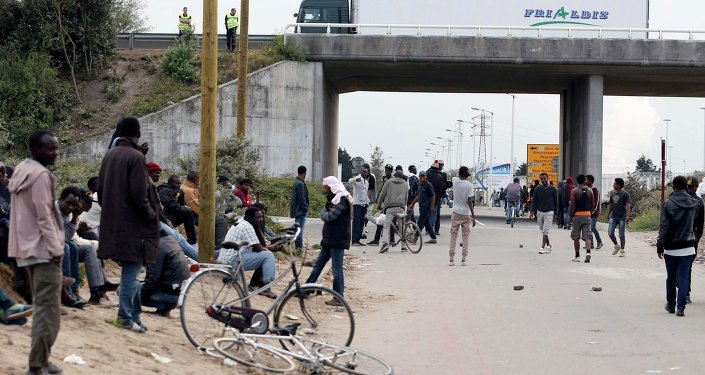 Migrants stand near a highway overpass near the makeshift camp called The New Jungle in Calais, France.