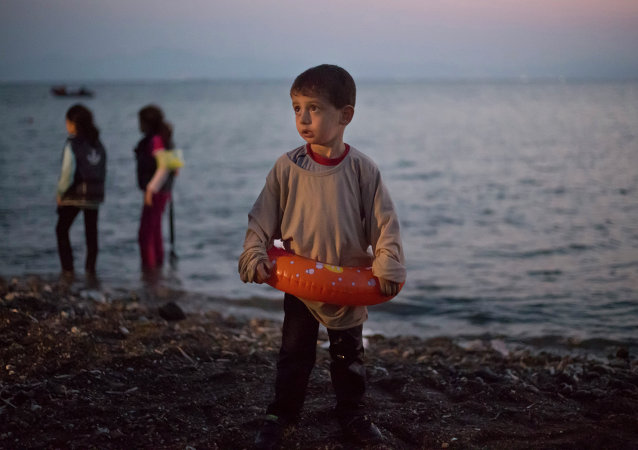 A Syrian migrant boy still wearing a swimming ring stands on the beach upon his arrival with other migrants by a dinghy at the southeastern Greek island of Kos, Greece, early Thursday, Aug. 20, 2015.