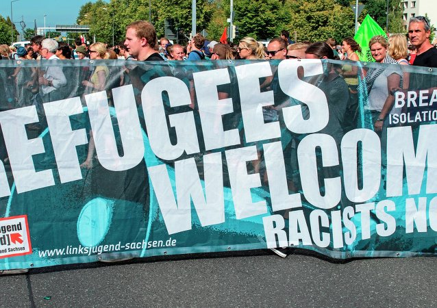 Protesters demonstrate with a banner 'Refugees welcome!' in Dresden, eastern Germany, Saturday, Aug. 29, 2015. A refugee shelter was attacked by far-right protesters in Heidenau near Dresden over the last weekend.