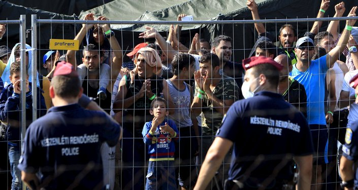 Migrants watch from behind a fence as Hungarian riot police stands guard in front of a migrant reception centre in Roszke, Hungary, September 4, 2015