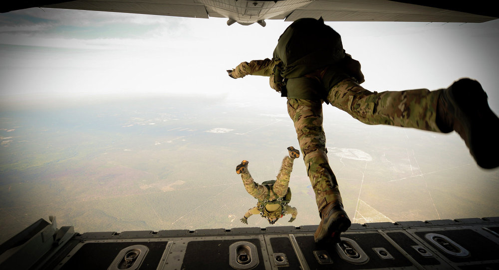 US Army Green Berets from the 7th Special Forces Group jump out of a C-130H3 Hercules