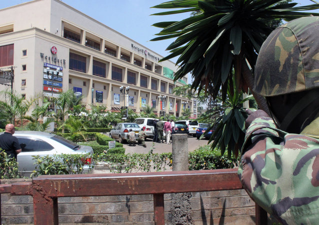 A soldier aims his weapon outside the Westgate Mall, an upscale shopping mall in Nairobi, Kenya Saturday Sept. 21 2013, where shooting erupted when armed men staged an attack.