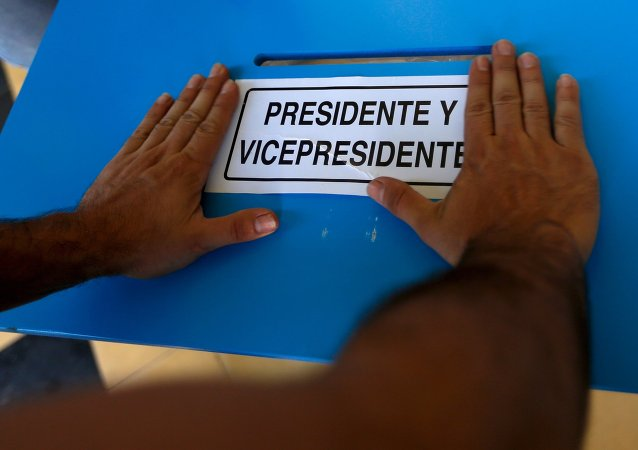 A electoral worker places a sign to mark the ballot box for President and Vice-President while installing a polling station at a school in Guatemala City, September 5, 2015