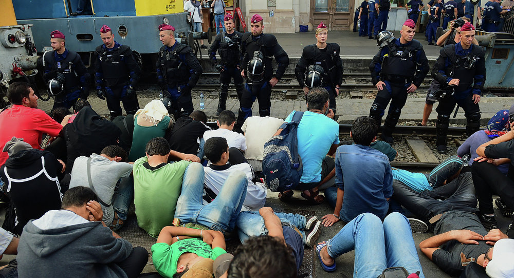Riot police stand on the train track as they monitor migrants and refugees at the Keleti (eastern) railway station in Budapest on September 1, 2015