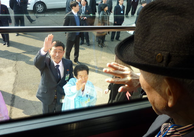 South Korean man waves to his North Korean relatives from the window of a bus following a family reunion at the resort area of Mount Kumgang, North Korea