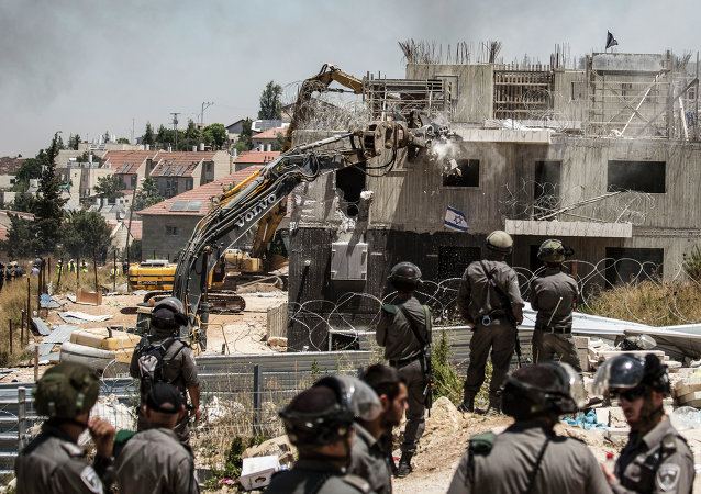 Israeli officers from the Border Patrol watch over the demolition of a building at the Jewish settlement of Beit El, near the West Bank town of Ramallah, Wednesday, July 29, 2015.