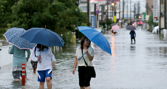 Pedestrians wade through flood waters on a road following torrential rains brought on by Typhoon Etau in Hamamatsu, Shizuoka prefecture, central Japan on September 8, 2015