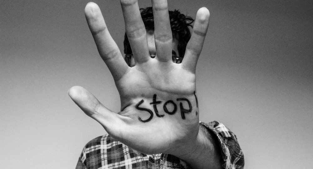 The word 'stop' written on a man's hand