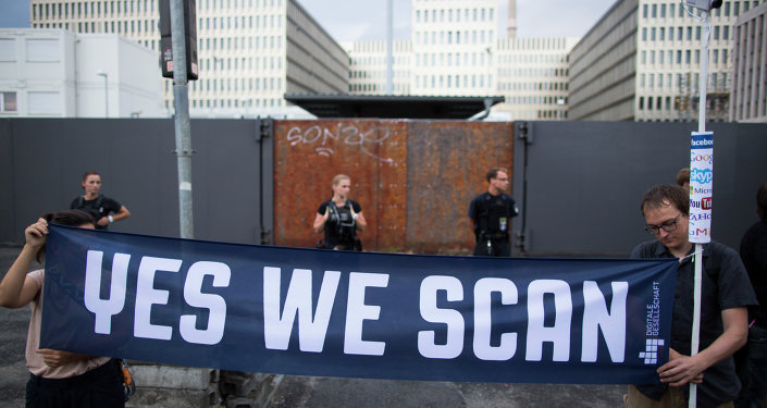 Demonstrators hold a banner during a protest against the supposed surveillance by the US National Security Agency, NSA, and the German intelligence agency, BND, during a rally in front of the construction site of the new headquarters of German intelligence agency in Berlin, Germany, Monday July 29, 2013.