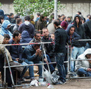 Refugees and migrants wait outside the Berlin State Office for Health and Social Affairs in Berlin, Germany, Friday Sept. 11, 2015