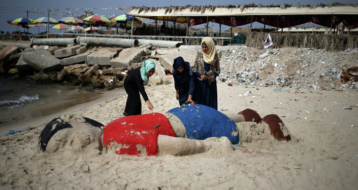 Palestinian girls put flowers on a sand sculpture by Indian artist Sudarsan Pattnaik depicting Syrian boy Aylan Kurdi, a three-year-old boy who drowned off Turkey, on September 7, 2015, on Gaza city beach