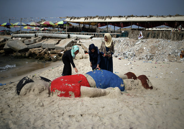 Palestinian girls put flowers on a sand sculpture depicting Syrian boy Aylan Kurdi, a three-year-old boy who drowned off Turkey, on September 7, 2015, on Gaza city beach