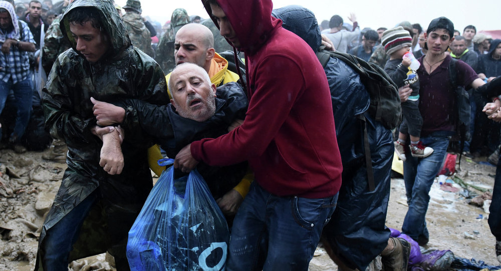 Migrants help an elderly man to pass from the northern Greek village of Idomeni to southern Macedonia, Thursday, Sept. 10, 2015. Thousands of people, including many families with young children, braved torrential downpours to cross Greeceís northern border with Macedonia early Thursday, after Greek authorities managed to register about 17,000 people on the island of Lesbos in the space of a few days, allowing them to continue their journey north into Europe.