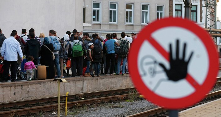 Migrants queue on the platform, waiting for a train at Vienna west railway station, Austria September 13, 2015