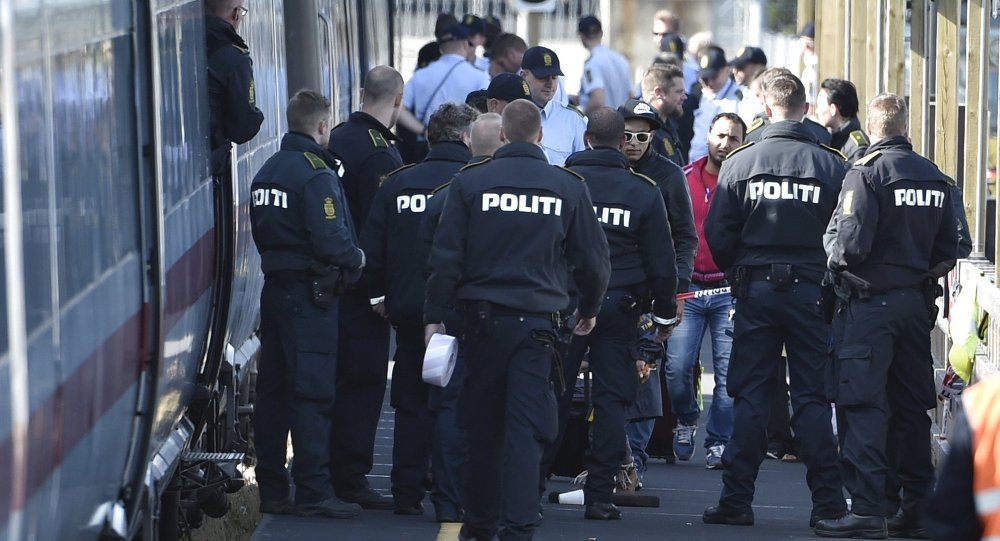 Danish police guard a train carrying migrants, mainly from Syria and Iraq, at Rodby train station, south of Denmark, September 9, 2015