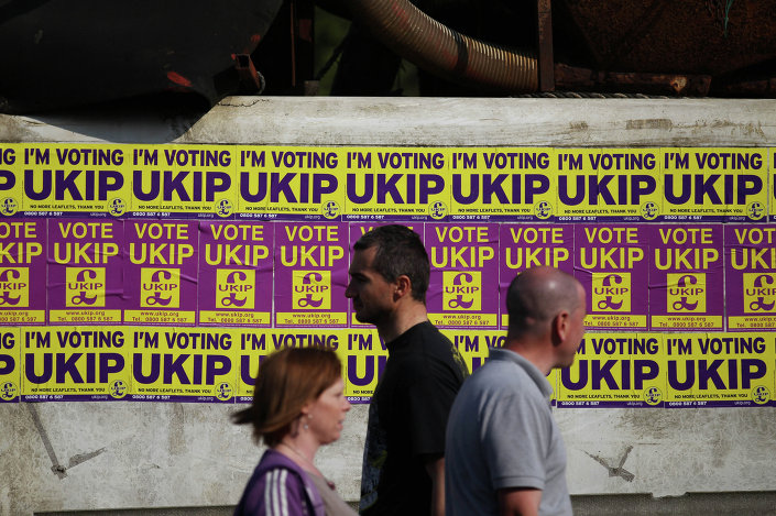 Local residents pass UK Independence Party general election campaign flyers