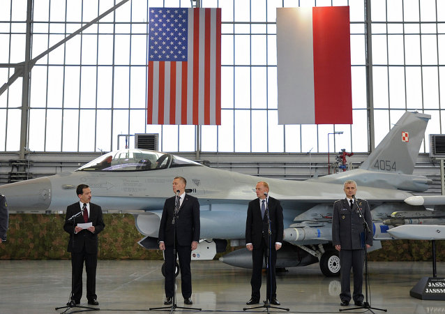 Polish and US officials stand in front of a F-16 fighter jet during the contract signing ceremony of 40 Lockheed Martin's joint air-to-surface standoff missiles.