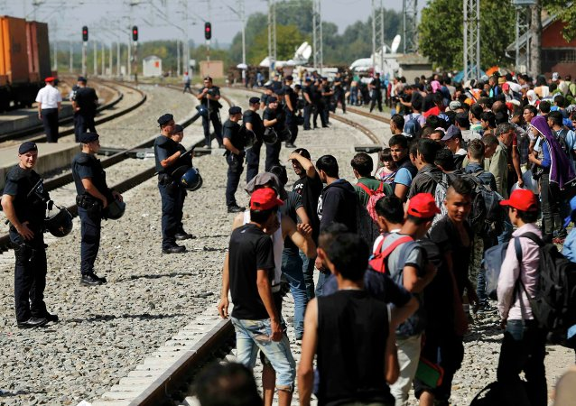 Police form a line in front of migrants at the railway station in Tovarnik, Croatia September 18, 2015