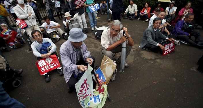 Protesters sitting on the ground with placards take part in a rally against Japan's Prime Minister Shinzo Abe's security bill and his administration in front of the parliament in Tokyo, September 18, 2015.