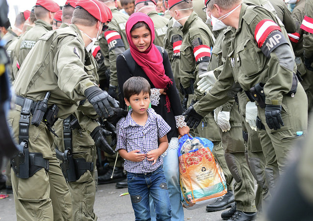 A migrant family is directed by Austrian soldiers at the Hungarian-Austrian border in Szentgotthard, Hungary, as thousands of migrants wait for their departure to Germany on September 19, 2015