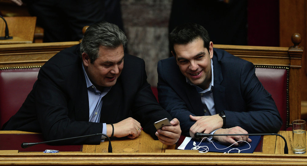 Greece's prime minister Alexis Tsipras (R) chats with member of coalition government and defense minister Panos Kammenos the confidence vote early on February 11, 2015.