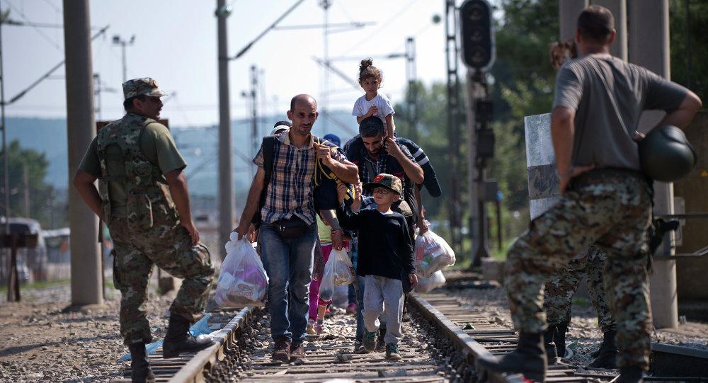 Migrants and refugees cross the Macedonian-Greek border near Gevgelija on September 20, 2015