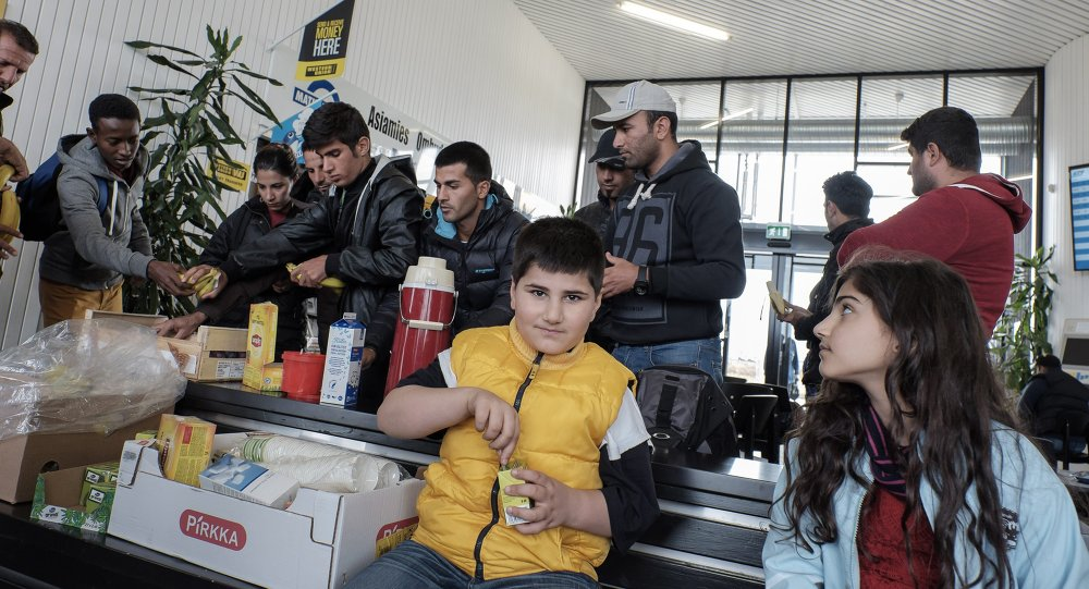 Refugees receive food upon arrival at the Tornio-Haaparanta bus station in Sweden after crossing the Finnish border on September 14, 2015
