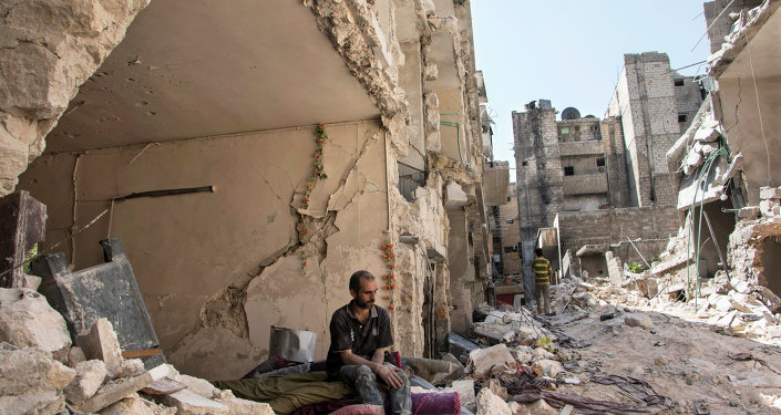 A Syrian man sits in the rubble following a barrel bomb attack the previous day on the rebel-held neighbourhood of al-Mashad in the northern Syrian city of Aleppo on September 17, 2015