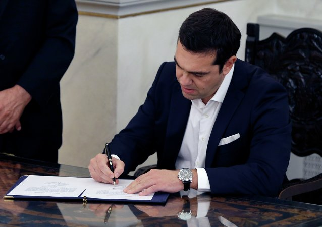 Leftwing leader Alexis Tsipras signs official documents after being sworn in as prime minister at a ceremony attended by President Prokopis Pavlopoulos in Athens on Monday, Sept. 21, 2015