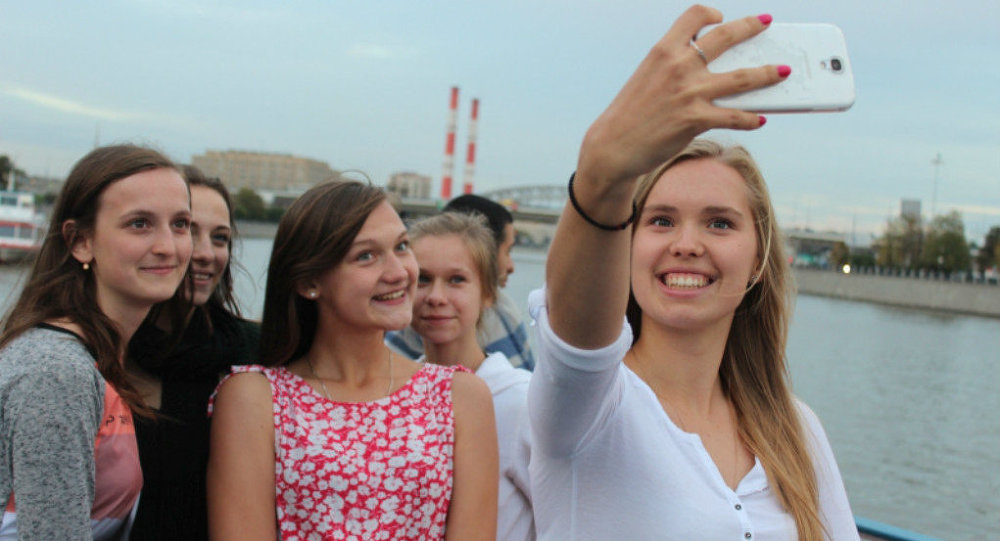 Polish literature and poetry students, arriving over the weekend for a weeklong trip to Russia, seen here posing for photos along the Moscow River.