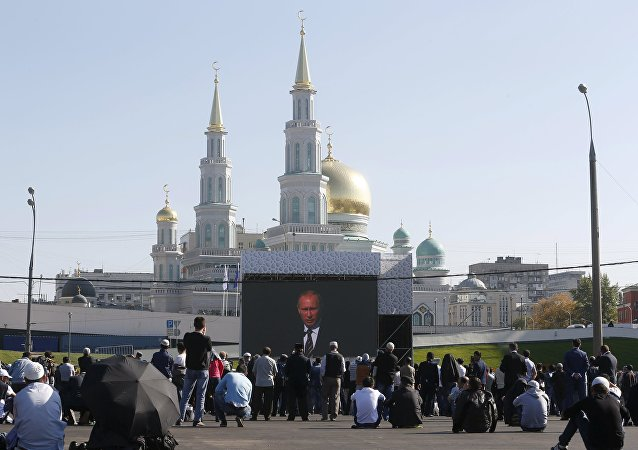People listen to Russian President Vladimir Putin as he delivers a speech at a ceremony to open the Moscow Grand Mosque in Moscow, Russia, September 23, 2015