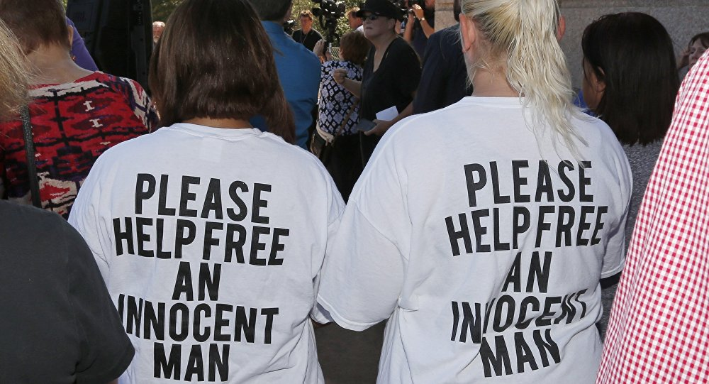Two women listen during a rally to stop the execution of Richard Glossip in Oklahoma City on September 15, 2015.