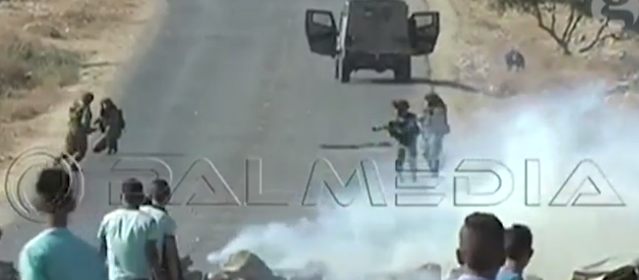 A military vehicle chases down Bernardi, who, knelt at right, attempts to pick up his camera.
