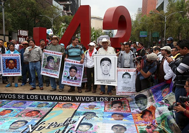 Relatives hold pictures of some of the 43 missing students of Ayotzinapa College Raul Isidro Burgos during a march to mark the first anniversary of their disappearance, in Mexico City, September 26, 2015